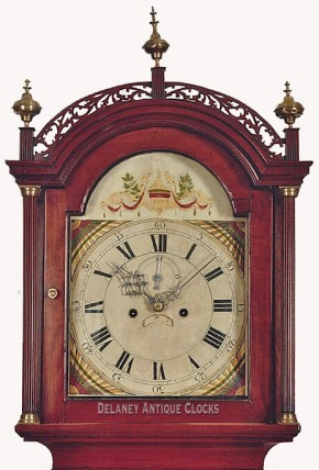 A New England tall clock.  The cherry case features cross banded veneers.